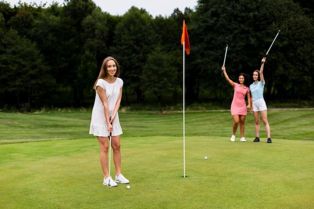 Un groupe complet de filles jouant au golf Photo gratuit