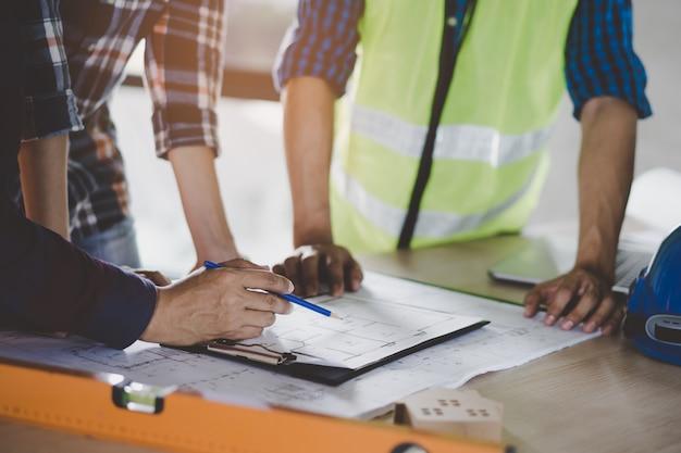 Groupe de constructeurs planifiant et discutant des dessins de maisons de construction. Photo Premium