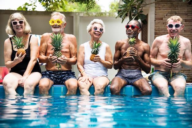 Groupe de divers adultes âgés assis au bord de la piscine, tenant des ananas ensemble Photo Premium