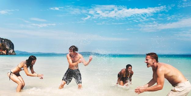Groupe diversifié d'amis jouant dans l'eau de la plage Photo gratuit
