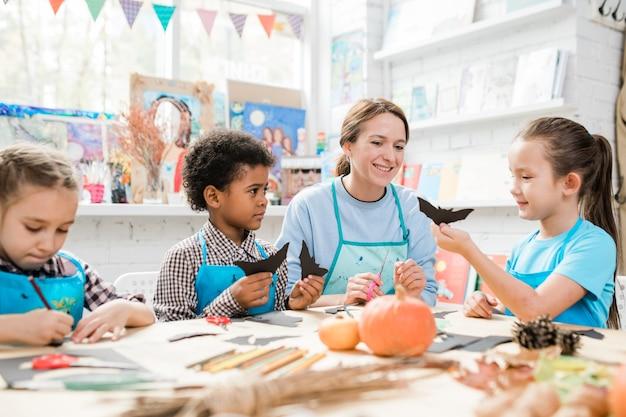 Groupe D'écoliers Diligents Contemporains Faisant Des Jouets D'halloween Et Les Montrant à Un Enseignant Heureux Photo Premium