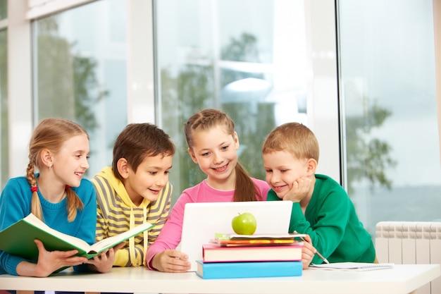 Groupe d'écoliers qui cherchent à ordinateur portable dans la classe Photo gratuit
