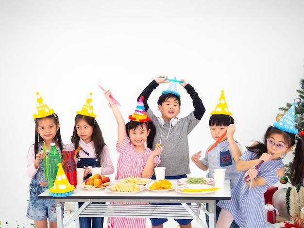Un groupe d'enfants célèbre la fête et s'amuse avec noël, les enfants échangent des cadeaux. Photo Premium