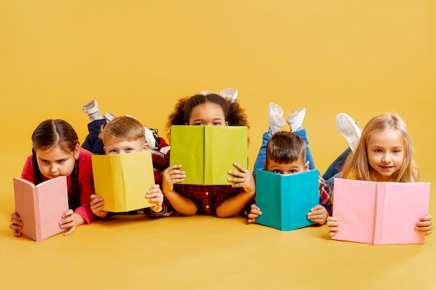 Groupe D'enfants Couvrant Leurs Visages Avec Des Livres Photo gratuit