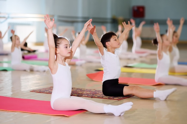 Un groupe d'enfants dans une école de ballet ou dans une section de gymnastique sur carimat Photo Premium