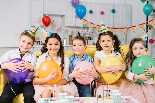 Groupe d'enfants heureux avec ballon assis sur un canapé Photo gratuit