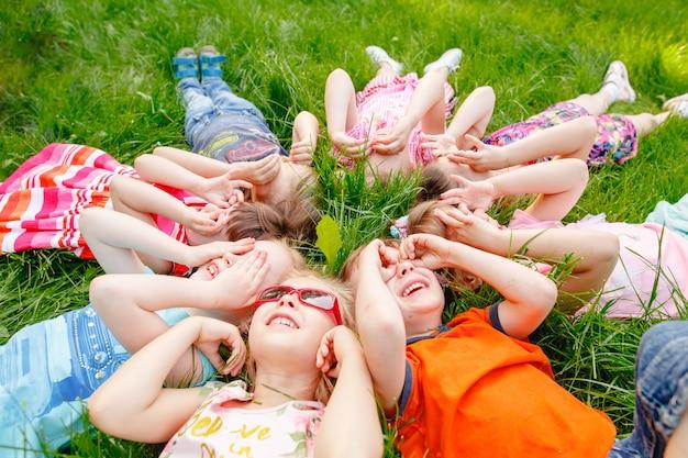 Un groupe d'enfants heureux de garçons et de filles courent dans le parc sur l'herbe par une journée d'été ensoleillée Photo Premium