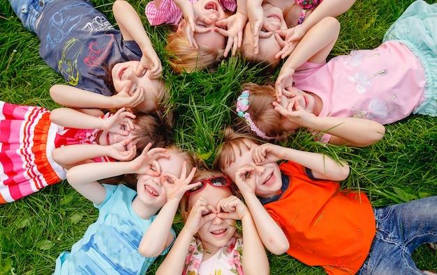 Un groupe d'enfants jouant et courant dans le parc sur un gozon vert. Photo Premium