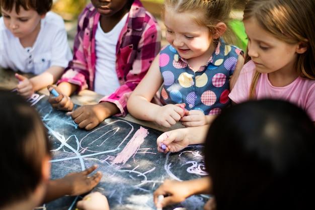 Groupe d'enfants de maternelle enfants dessinant des cours d'art en plein air Photo Premium