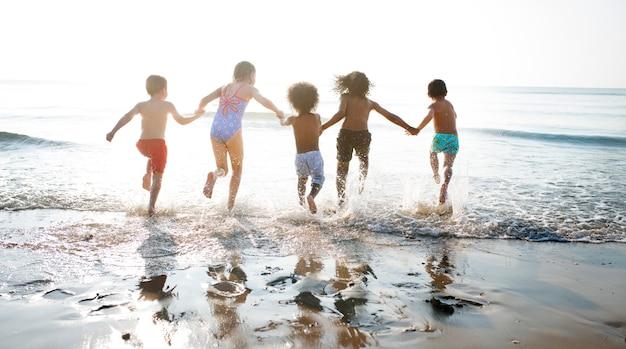 Groupe d'enfants profitant de leur temps à la plage Photo Premium