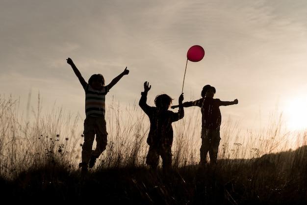 Groupe d'enfants profitant de leur temps sur la prairie au coucher du soleil Photo Premium