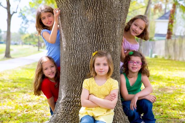 Groupe d'enfants de soeurs filles et amis sur le tronc d'arbre Photo Premium