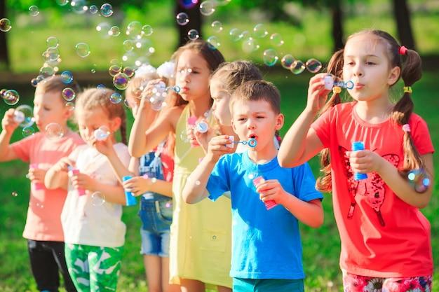Groupe D'enfants Soufflant Des Bulles De Savon Photo Premium