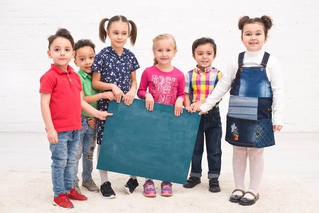Groupe d'enfants avec un tableau Photo gratuit