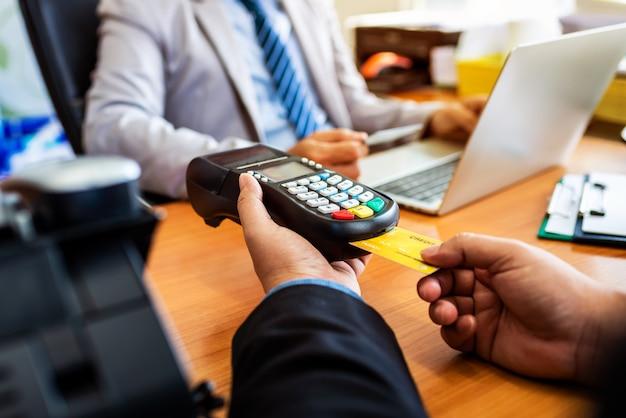 Groupe d'entreprise détenant une carte de crédit avec système de paiement nfc dans un bureau moderne. Photo Premium