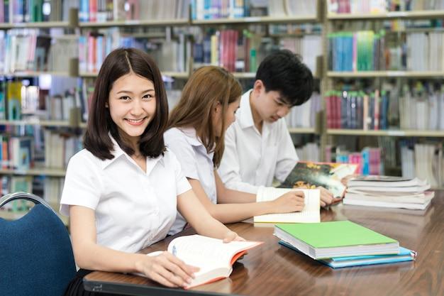 Groupe d'étudiants asiatiques en uniforme étudient ensemble dans la bibliothèque à l'université. Photo Premium