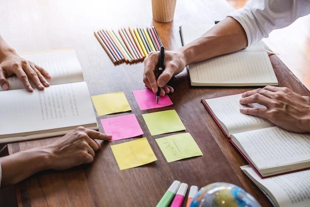 Groupe d'étudiants assis à la bibliothèque, étudiant, lisant, faisant ses devoirs et enseignant Photo Premium