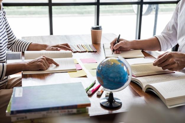 Groupe d'étudiants assis à un bureau dans une bibliothèque étudiant et lisant, faisant ses devoirs et ses leçons Photo Premium