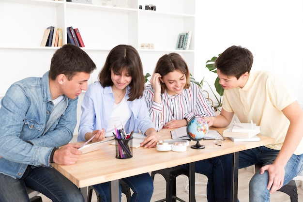 Groupe d'étudiants en bibliothèque Photo gratuit