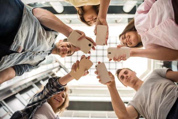 Groupe d'étudiants debout en cercle et à l'aide de téléphones. Photo Premium