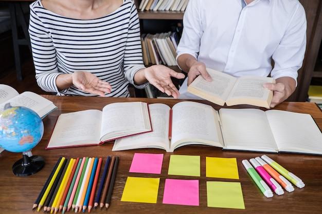 Groupe d'étudiants du secondaire ou du collège assis à son bureau dans une bibliothèque étudiant et lisant, faisant ses devoirs et ses leçons Photo Premium