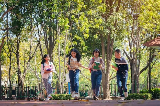 Groupe D'étudiants Jeunes Heureux Courir à L'extérieur, Divers Jeunes étudiants Livre Concept En Plein Air Photo Premium