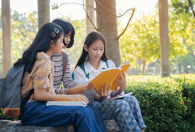 Groupe D'étudiants Jeunes Et Livre De Lecture De L'éducation Dans Le Parc De La Ville Photo Premium