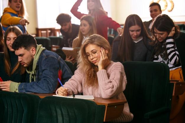 Le Groupe D'étudiants Joyeux Et Heureux Assis Dans Une Salle De Conférence Avant La Leçon Photo gratuit