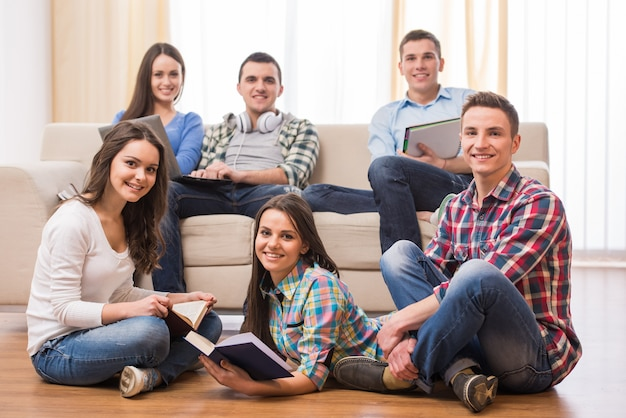 Groupe d'étudiants avec des livres et un ordinateur portable. Photo Premium