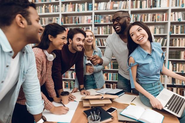 Groupe d'étudiants multiethniques parlant dans la bibliothèque. Photo Premium