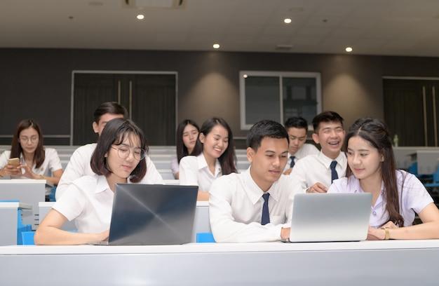 Groupe d'étudiants travaillant avec un ordinateur portable dans une salle de classe Photo Premium
