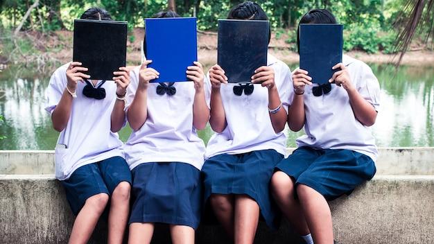 Le groupe d'étudiants en uniforme tenant livre. concept de meilleurs amis Photo Premium