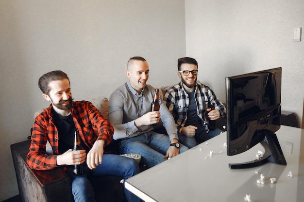 Un groupe de fans regarde le football à la télévision Photo gratuit
