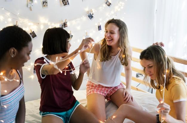 Groupe de femmes diverses s'amusant sur le lit ensemble Photo Premium