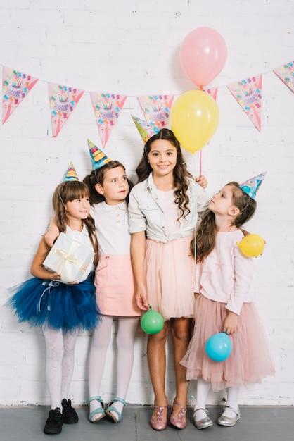 Groupe de filles debout contre le mur de briques blanches tenant des ballons et une boîte cadeau à la main Photo gratuit