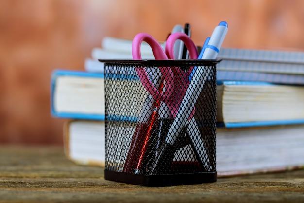 Groupe de fournitures scolaires et de livres sur fond de bois Photo Premium