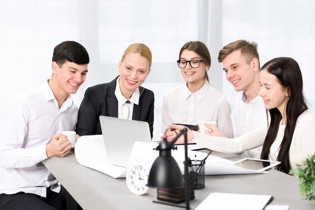 Groupe de gens d'affaires discutant du projet sur un ordinateur portable Photo gratuit