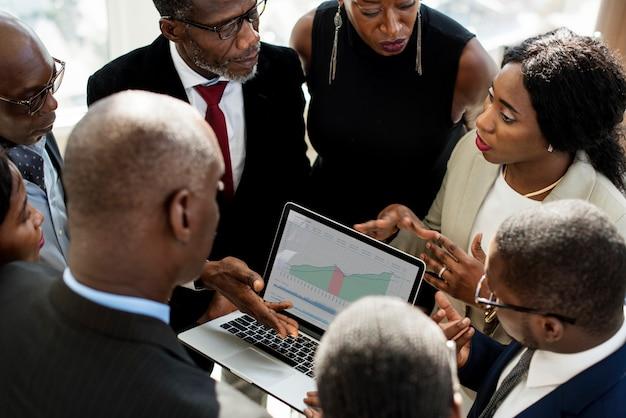 Un groupe de gens d'affaires internationaux discutant avec un ordinateur portable Photo Premium