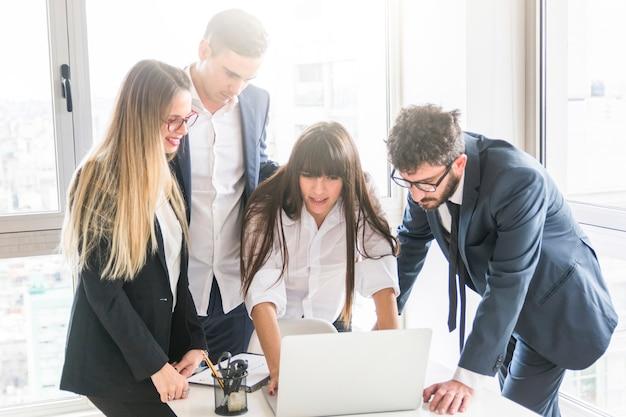 Groupe de gens d'affaires à la recherche d'un ordinateur portable au bureau Photo gratuit