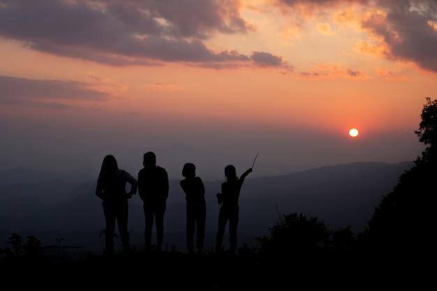Groupe de gens heureux jouant au coucher du soleil de l'été dans la nature Photo gratuit