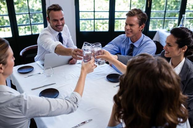Groupe d'hommes d'affaires portant un verre d'eau au restaurant Photo Premium