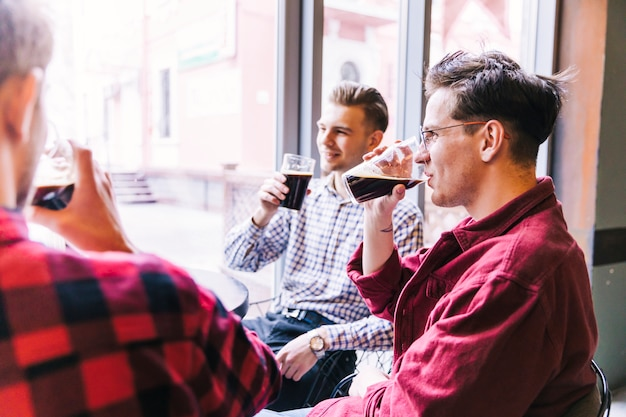 Groupe d'hommes buvant de la bière au bar Photo gratuit
