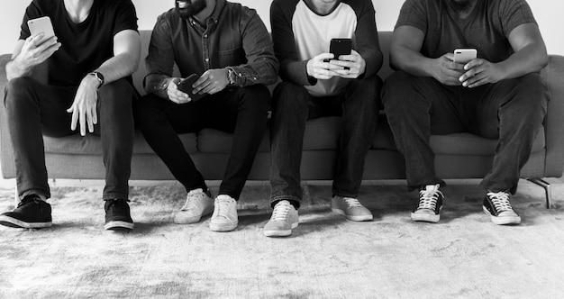 Groupe d'hommes divers utilisant le concept de médias sociaux et internet de téléphonie mobile Photo gratuit