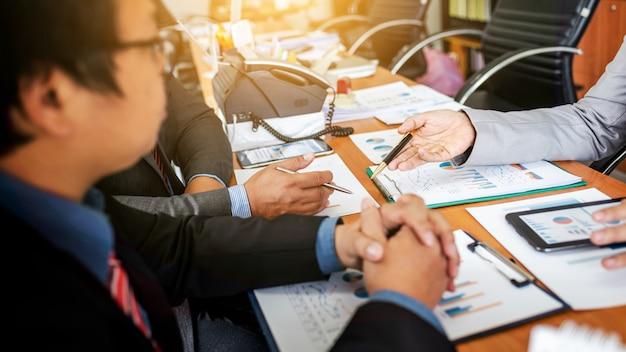 Groupe d'hommes entrepreneurs discutant d'un projet de gestion lors d'une collaboration Photo Premium