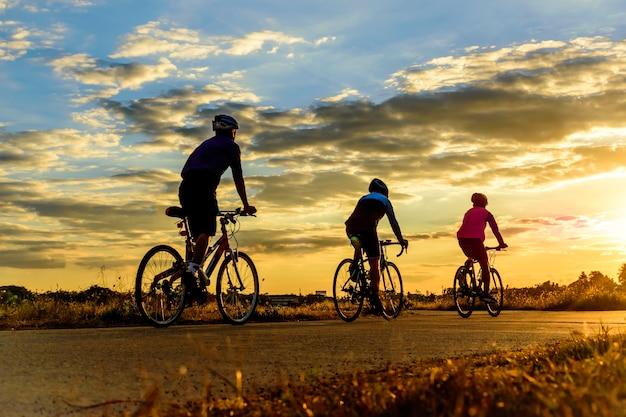 Groupe d'hommes faire du vélo au coucher du soleil. Photo Premium