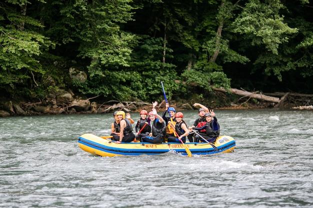 Groupe D'hommes Et De Femmes Font Du Rafting Sur La Rivière, Sport Extrême Et Amusant Photo Premium