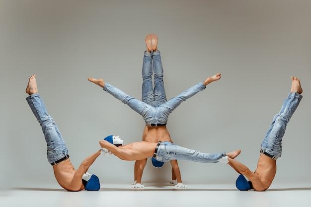 Le Groupe Des Hommes De Race Blanche Acrobatique Gymnastique Sur L'équilibre Pose Photo gratuit