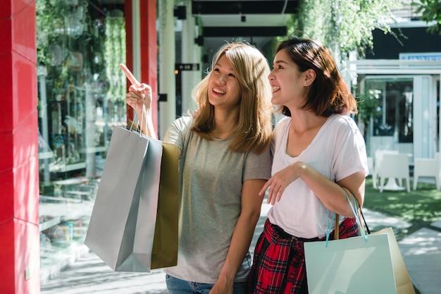 Groupe de jeune femme asiatique, faire du shopping dans un marché en plein air avec des sacs à provisions à la main Photo gratuit