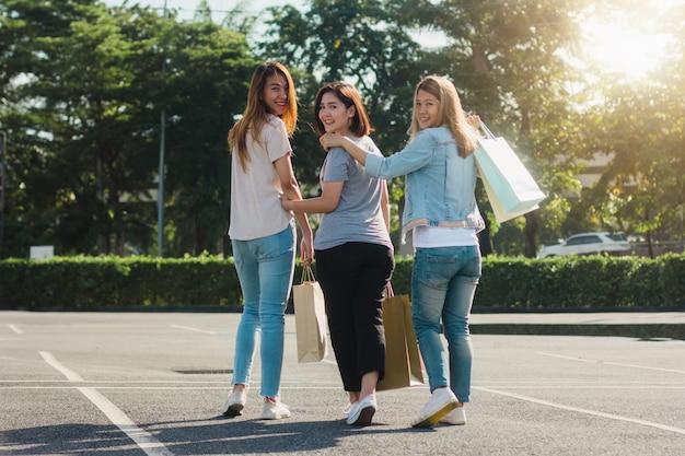 Groupe de jeune femme asiatique shopping dans un marché en plein air avec des sacs à provisions Photo gratuit