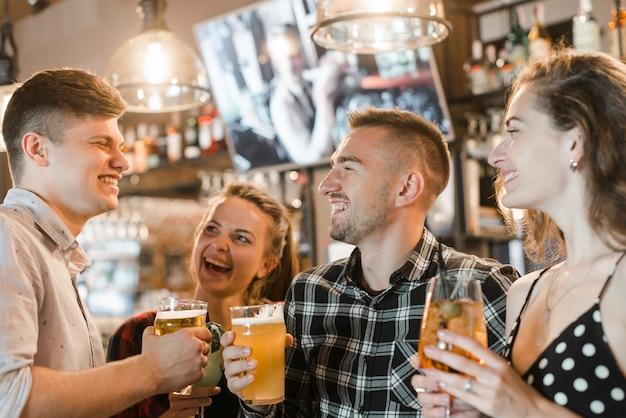 Groupe de jeunes amis appréciant dans le bar Photo gratuit